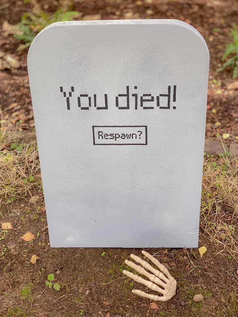 DIY Halloween tombstone with fake skeleton hand coming out of grave