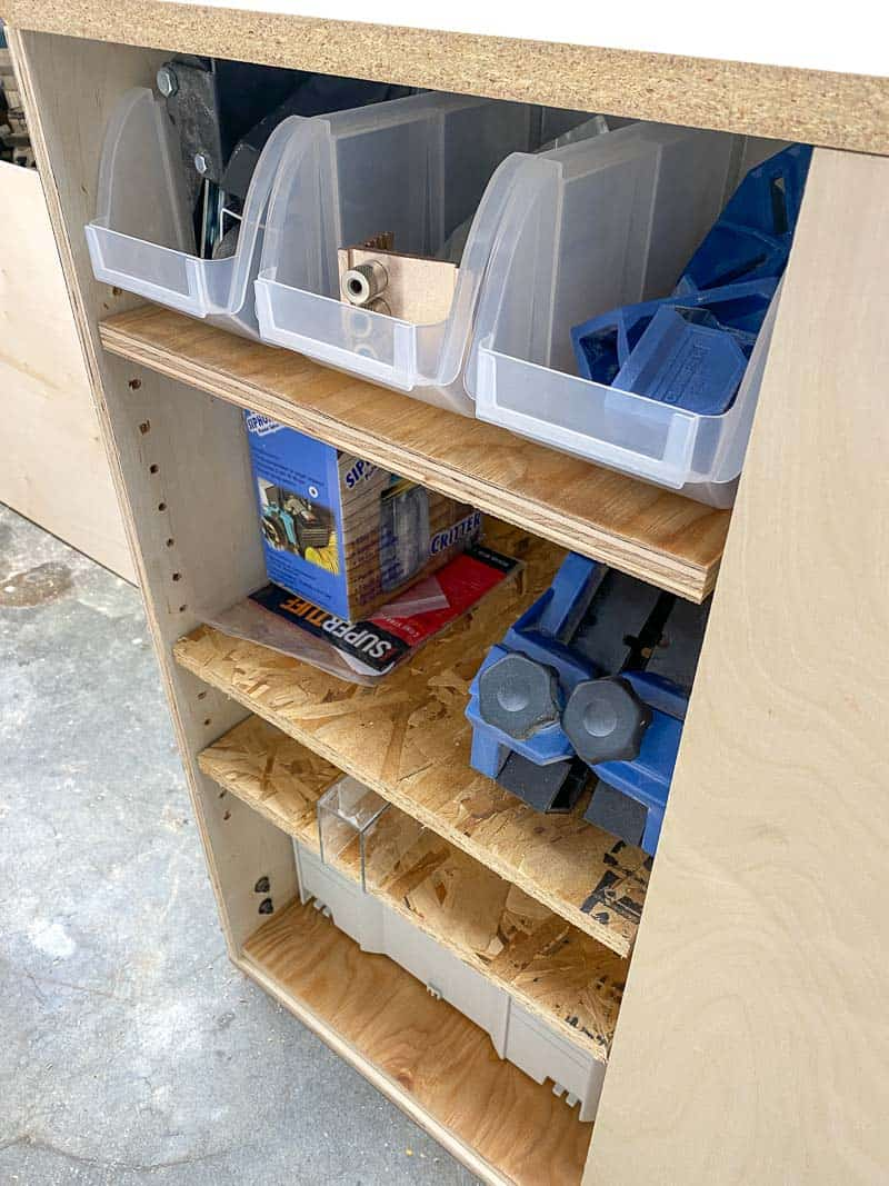 woodworking tools stored on shelves in table saw stand