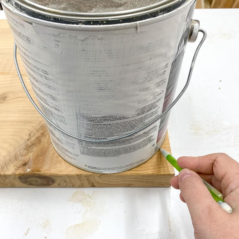 tracing rounded corners onto scrap wood with a paint can