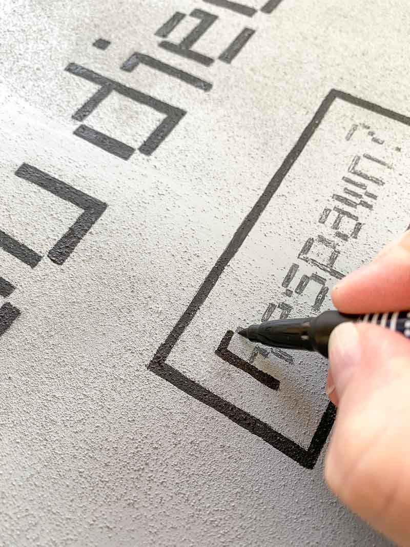 filling in the details of the DIY Halloween tombstones with a paint pen