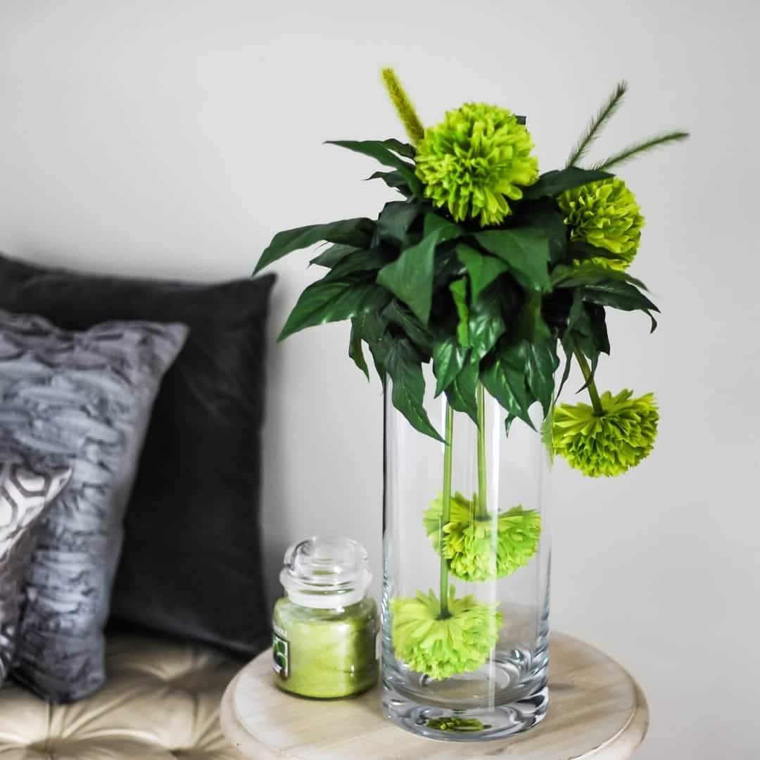 end table with flower arrangement and candle next to bed