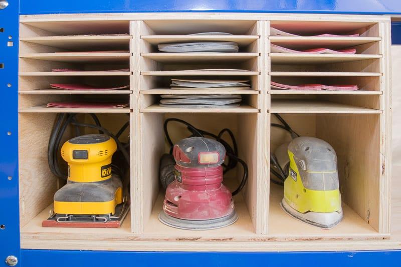 sanders and sandpaper organized in storage rack under workbench