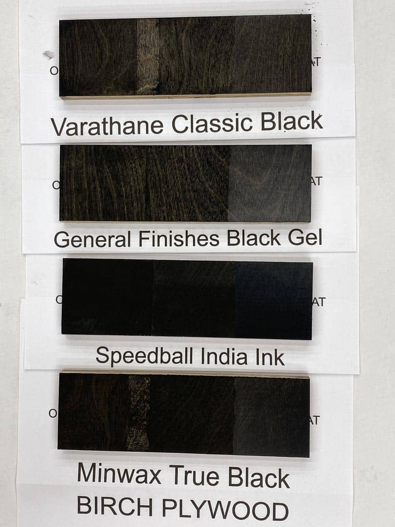 four black wood stain samples on birch plywood