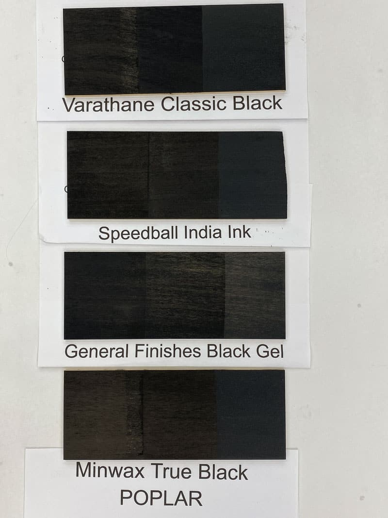 four black wood stain samples on poplar