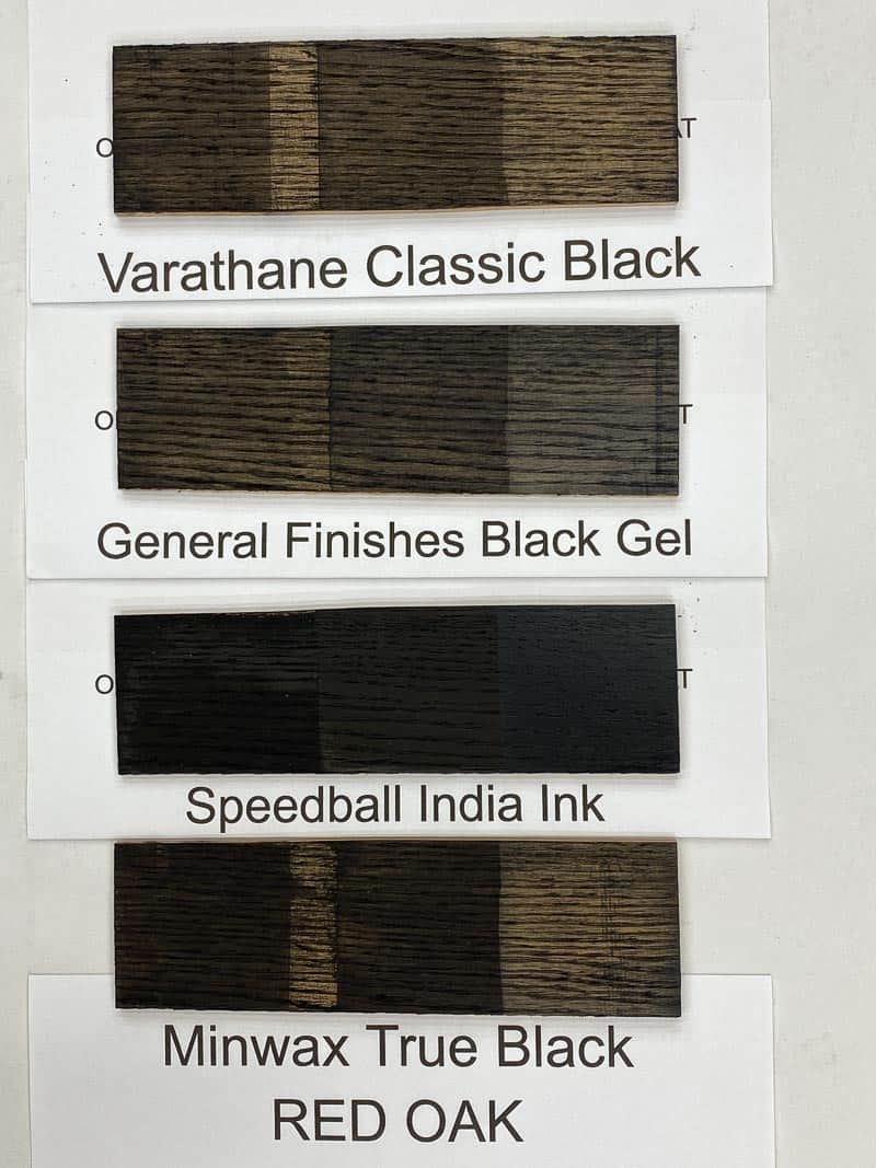 four black wood stain samples on red oak