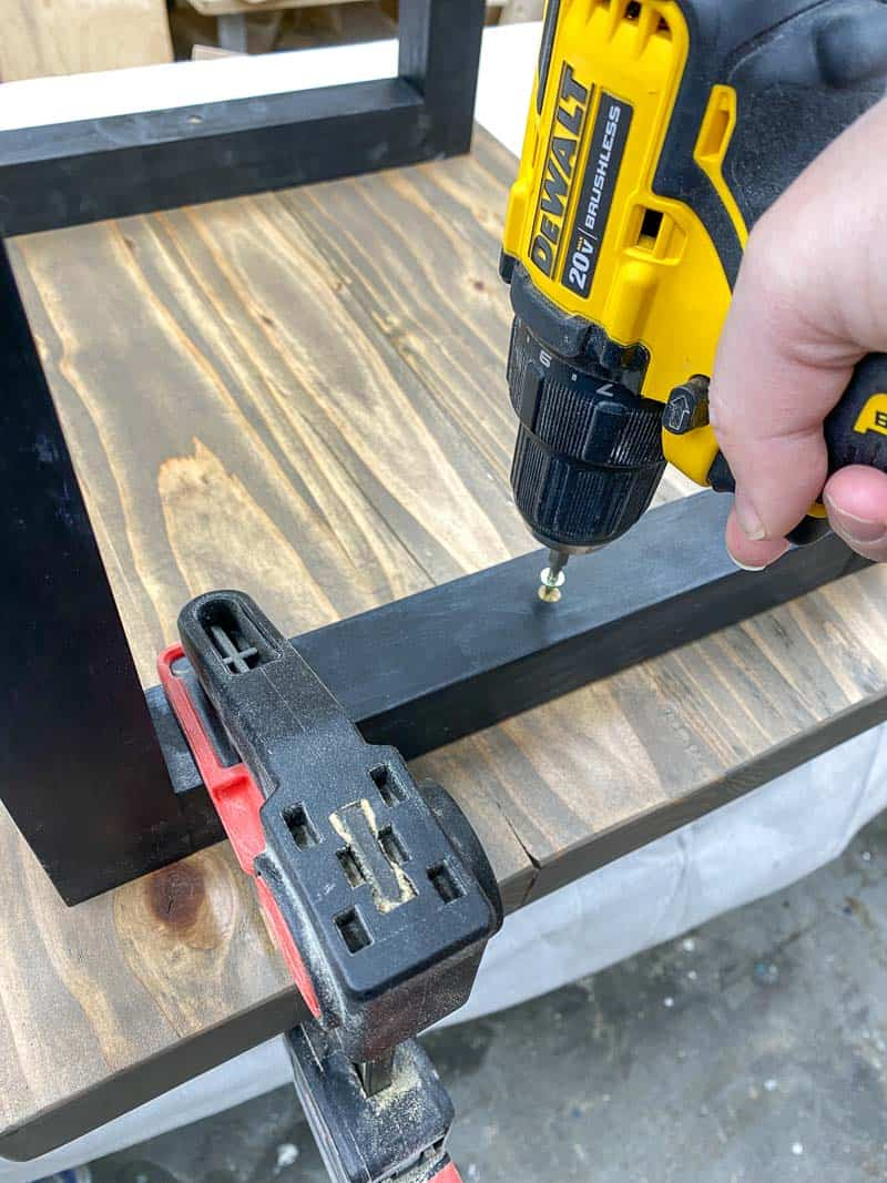 attaching the top of the DIY rustic end table to the legs with screws