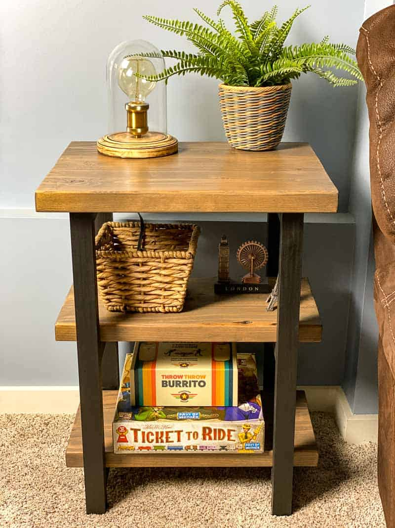 DIY rustic end table with shelves filled with baskets and board games