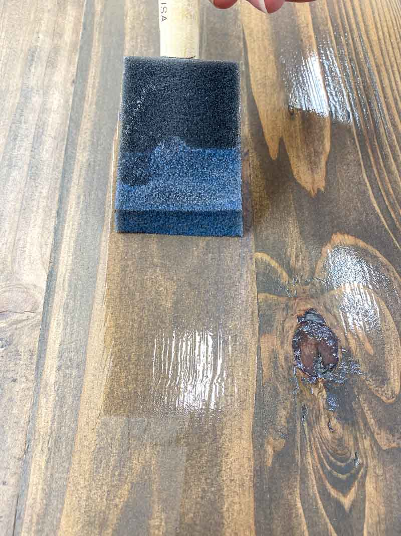 applying polycrylic to the rustic wood surface with a foam brush