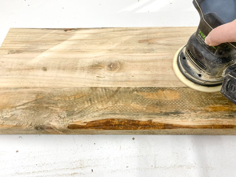 sanding the surface of the rustic end table shelves