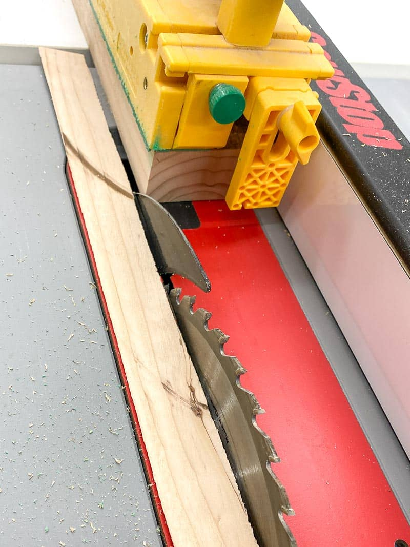 trimming rounded edges off 2x4 board at the table saw