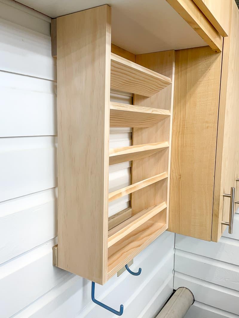 empty spray paint storage rack next to cabinet in workshop