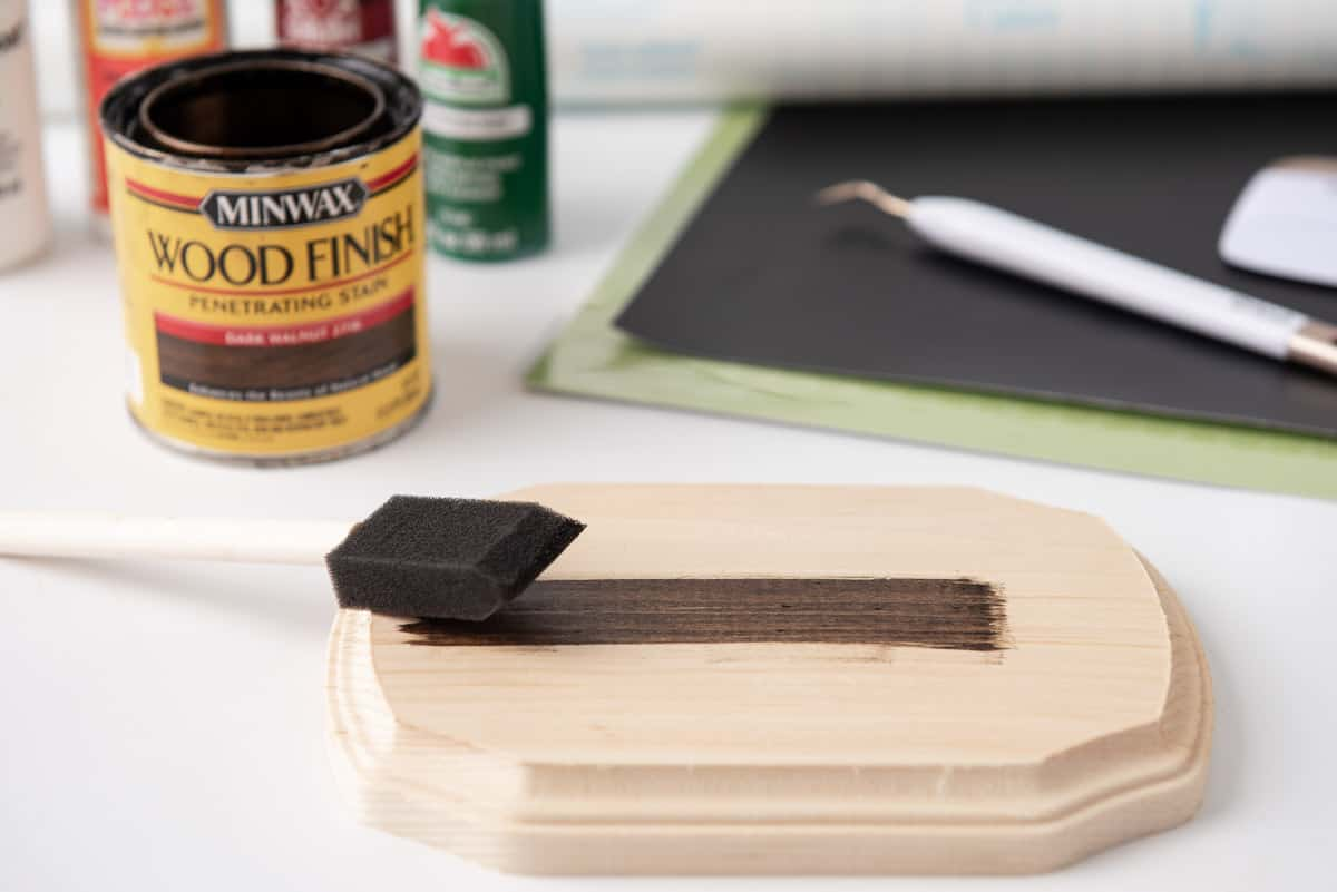 applying wood stain to plaque with a foam brush