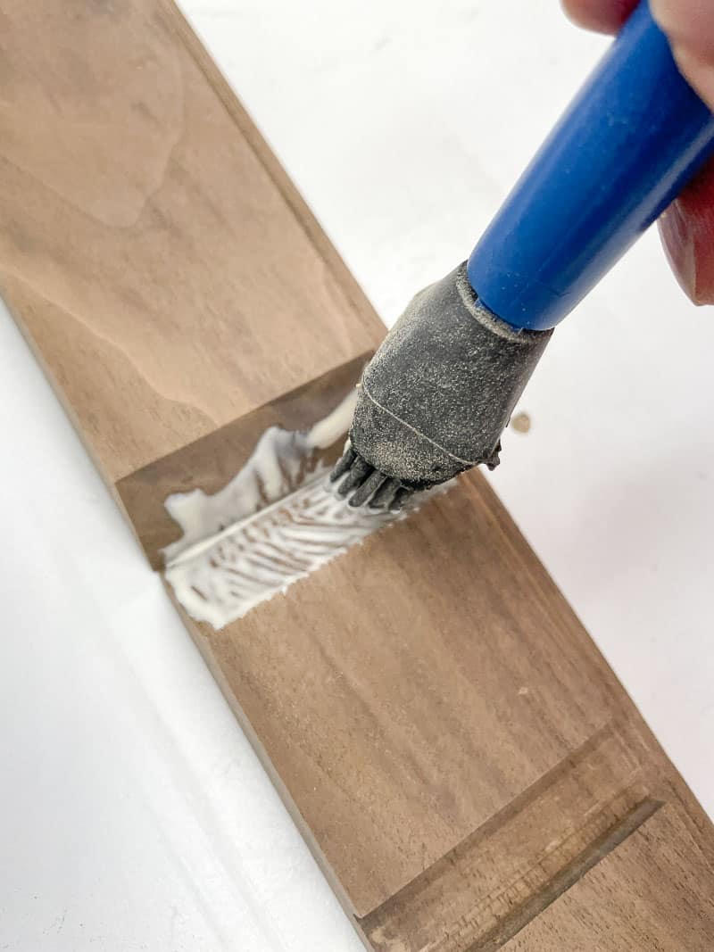 applying wood glue to mitered joint with a glue brush