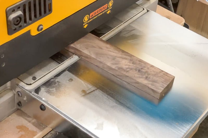 walnut board coming out of thickness planer
