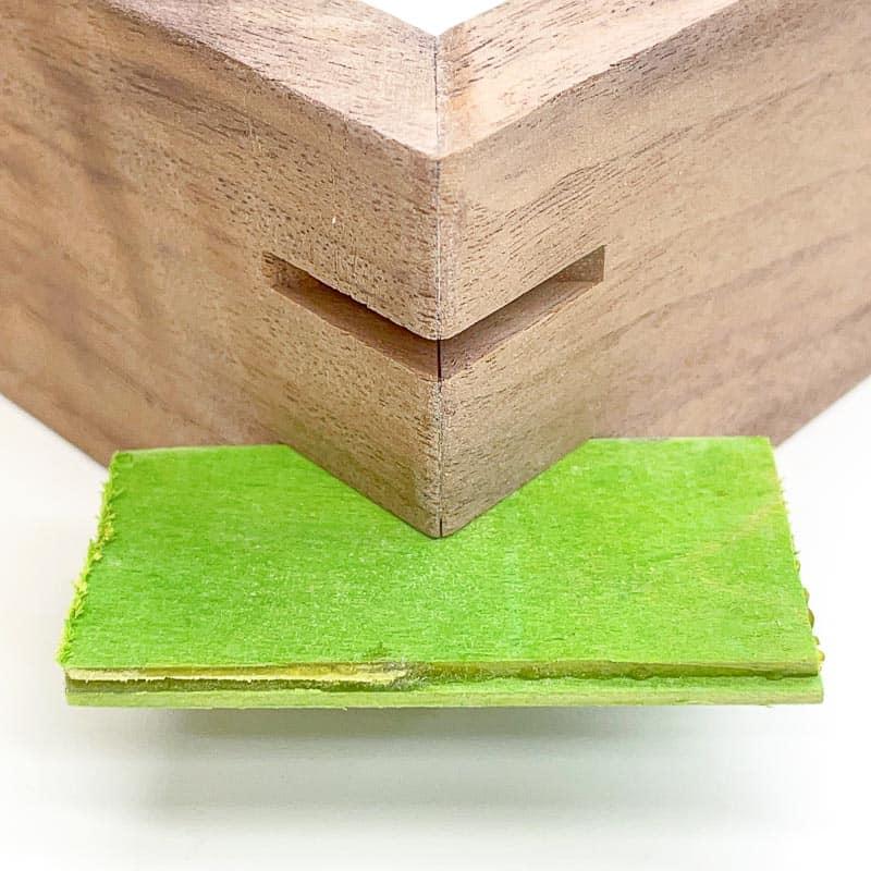 green wood veneer inserted into cut grooves in corners for splines