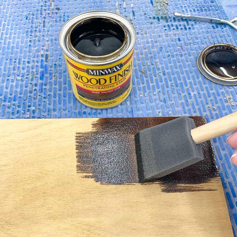 applying dark walnut wood stain to plywood with a foam brush