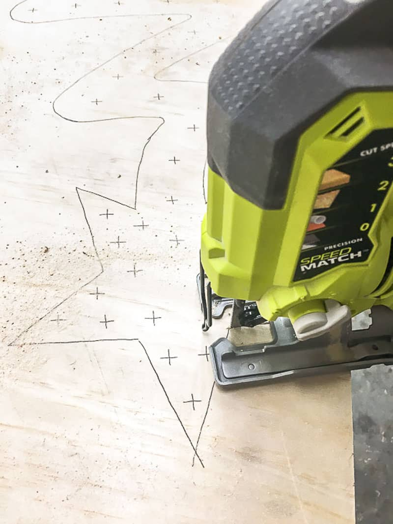 cutting out wooden Christmas tree from plywood with a jigsaw