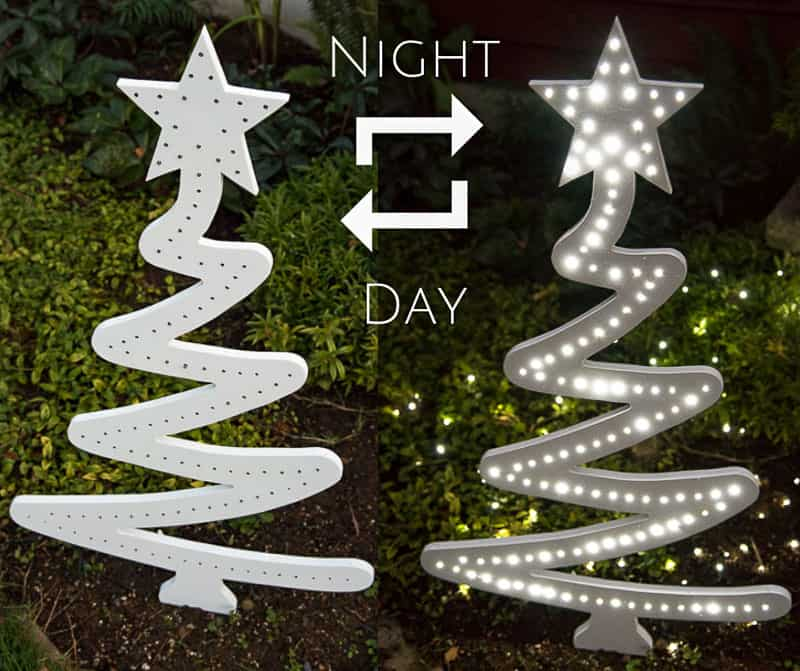 DIY wooden Christmas tree in yard during day and lit up at night