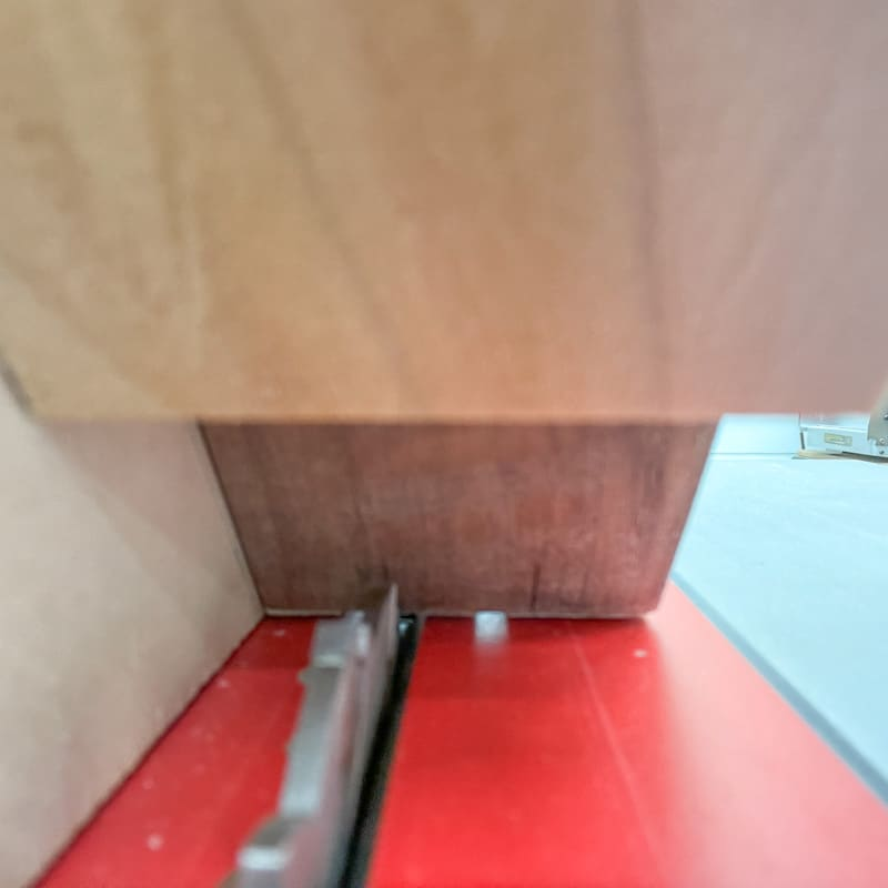 Lining up the table saw blade with the marks on the side of the box in the spline jig
