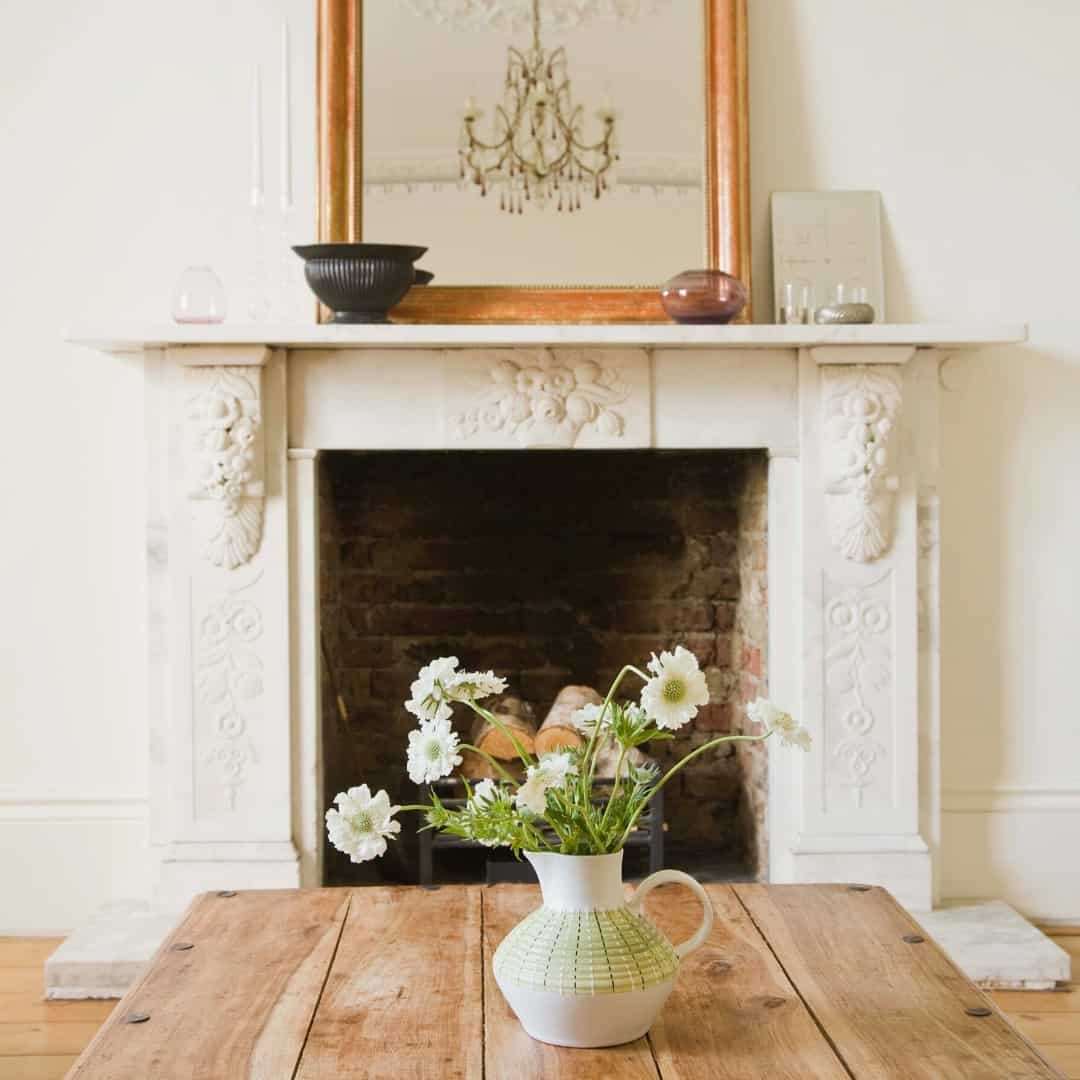 contrasting styles with ornate fireplace and farmhouse table