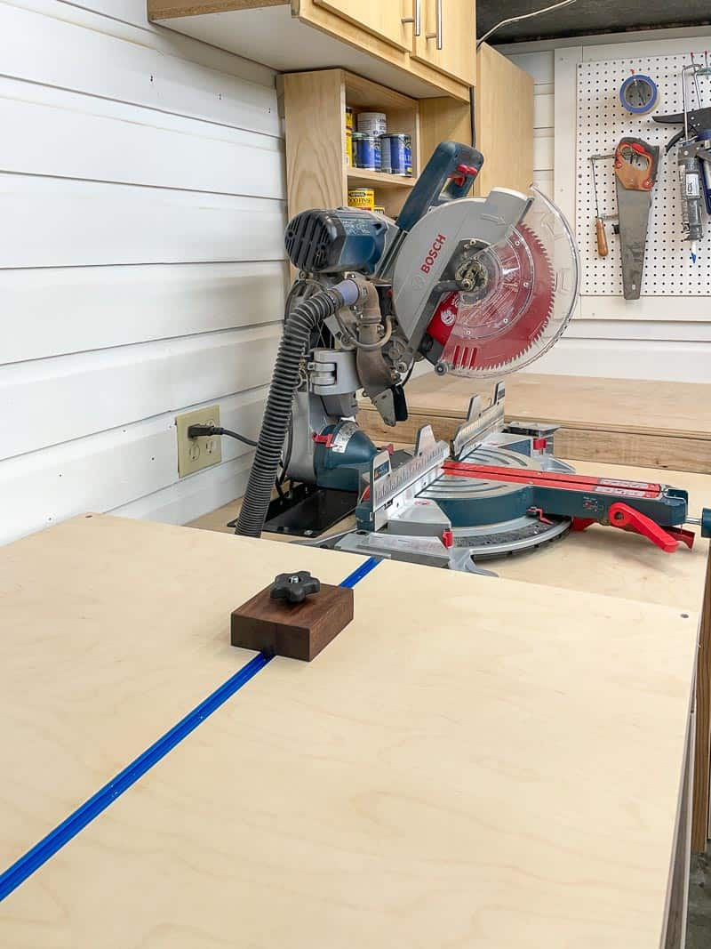 miter saw station with shelves and cabinets on the wall above