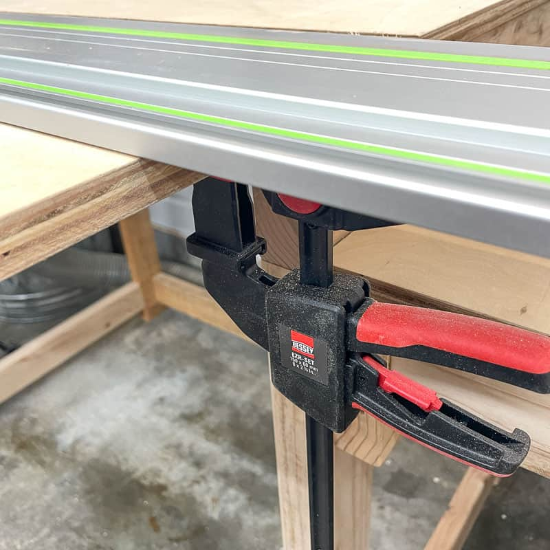 Bessey track saw clamp holding track to worksurface from underneath