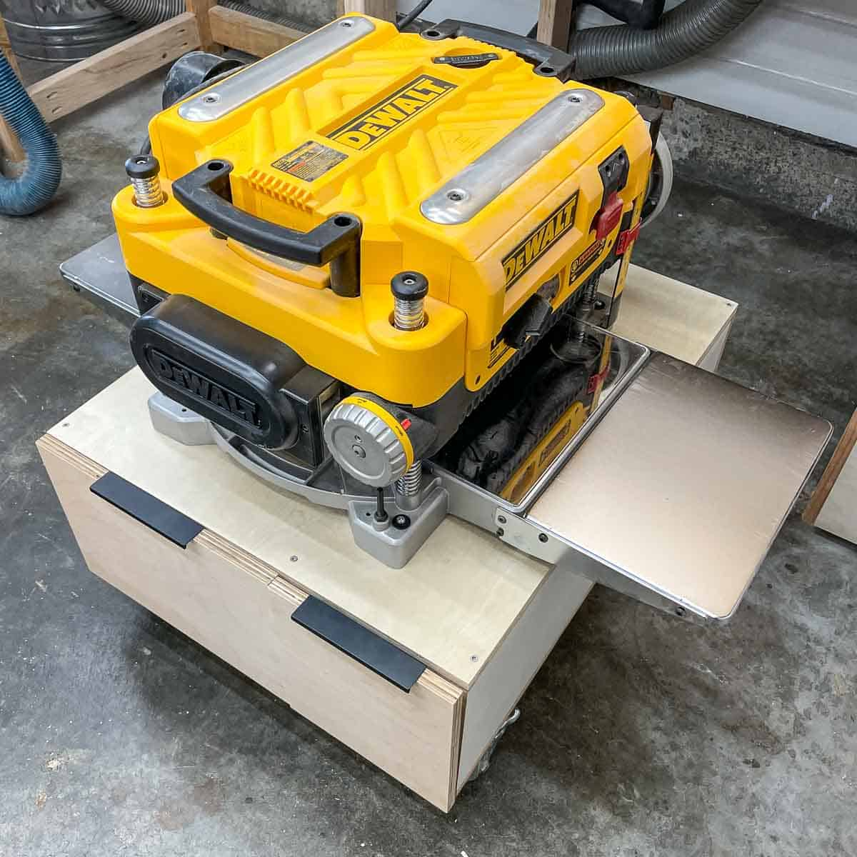 planer stand rolled out from under miter saw with infeed and outfeed tables installed
