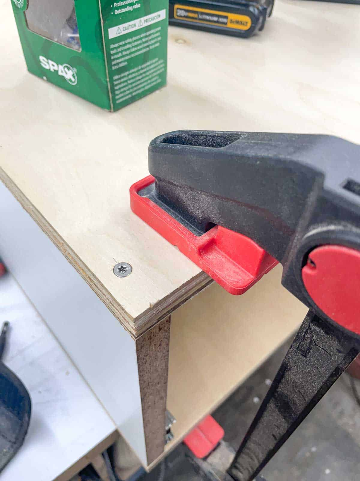 countersunk screws in top of planer stand with clamp holding pieces in place
