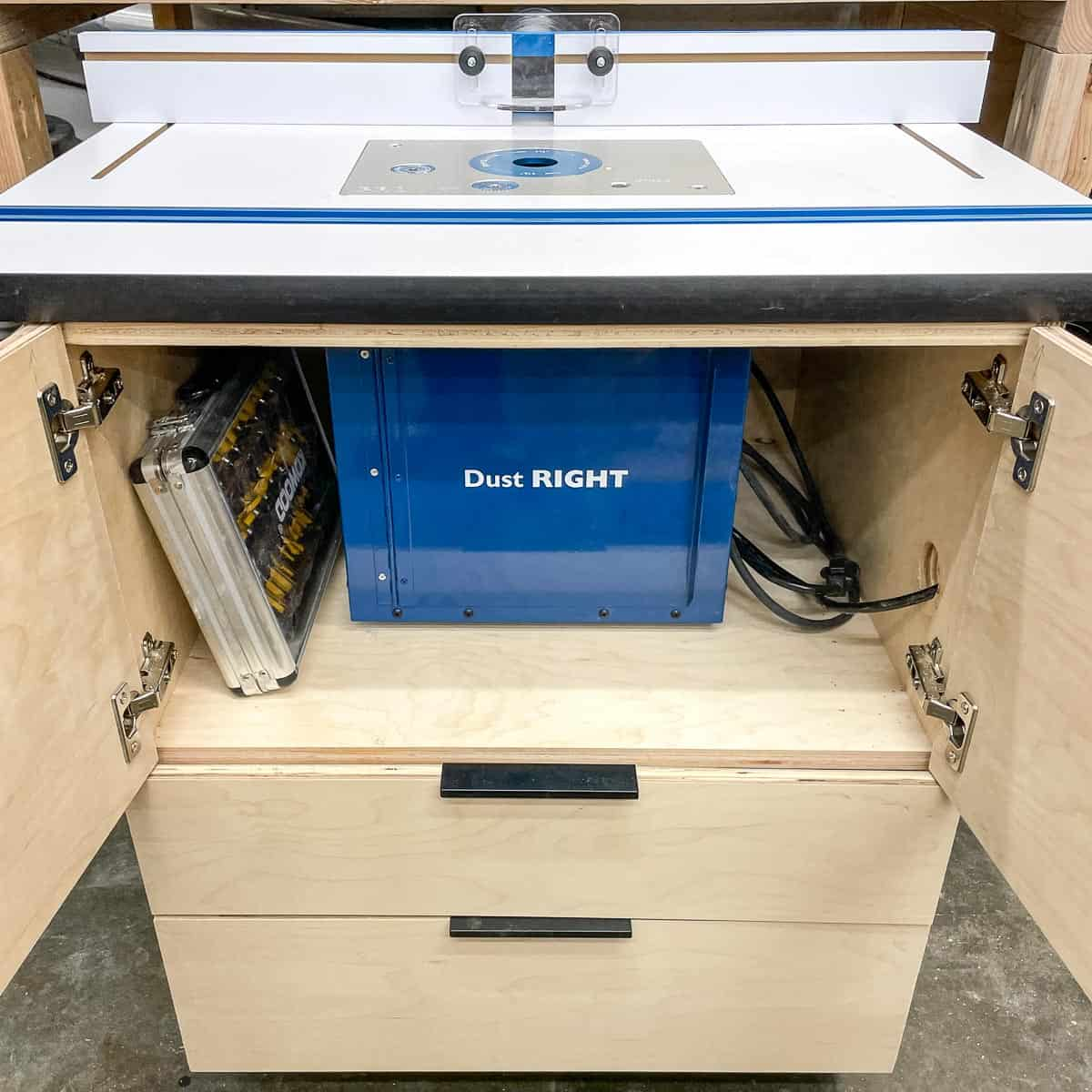 DIY router table with cabinet doors open to reveal dust bucket and router bit set