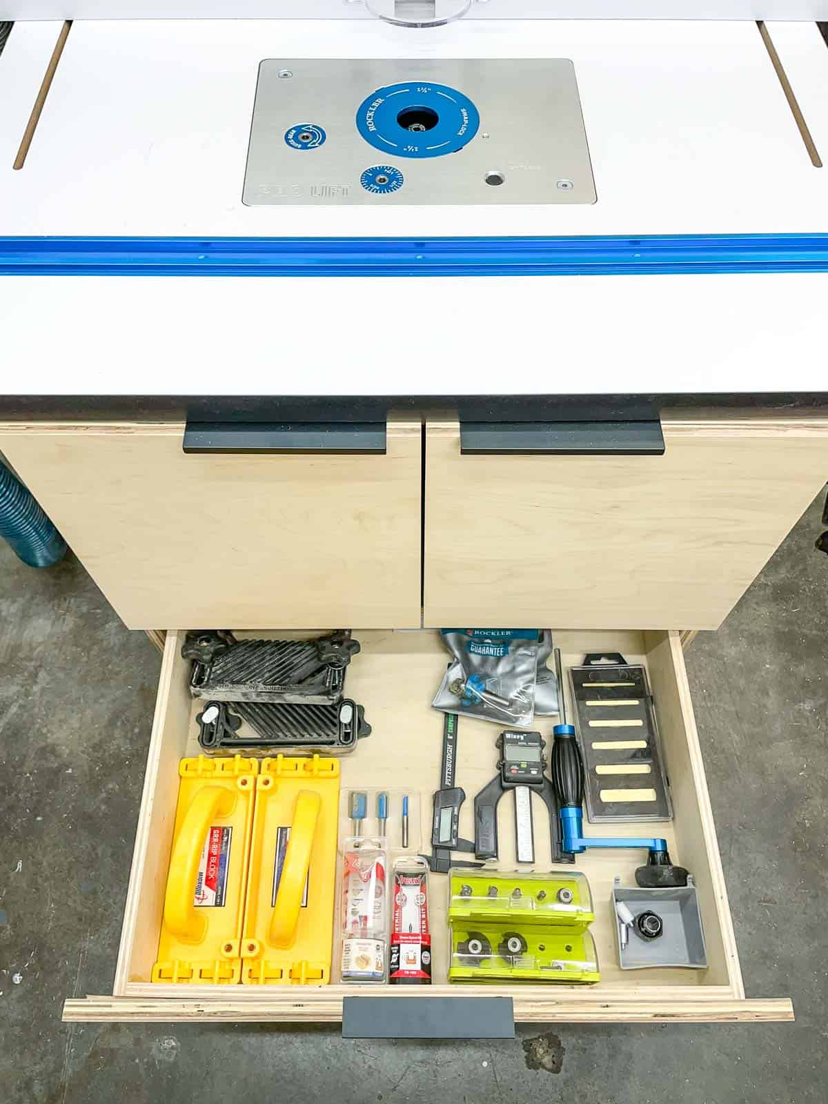 DIY router table with drawer pulled out to reveal routing tools and bits