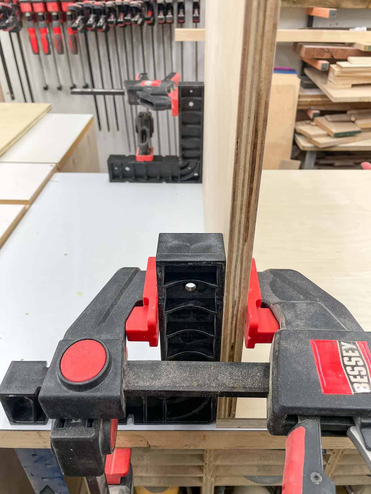 Right angle positioning squares and clamps holding router table sides at a 90 degree angle