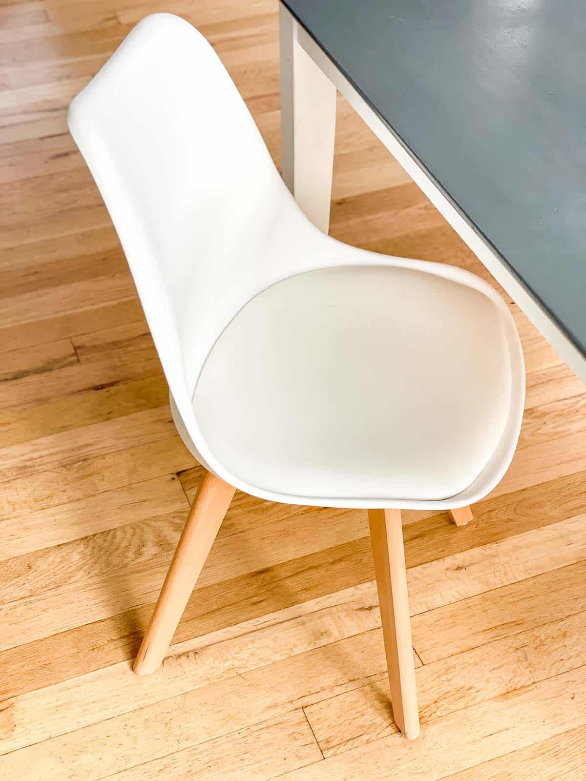 white midcentury modern tulip chair next to gray wood table