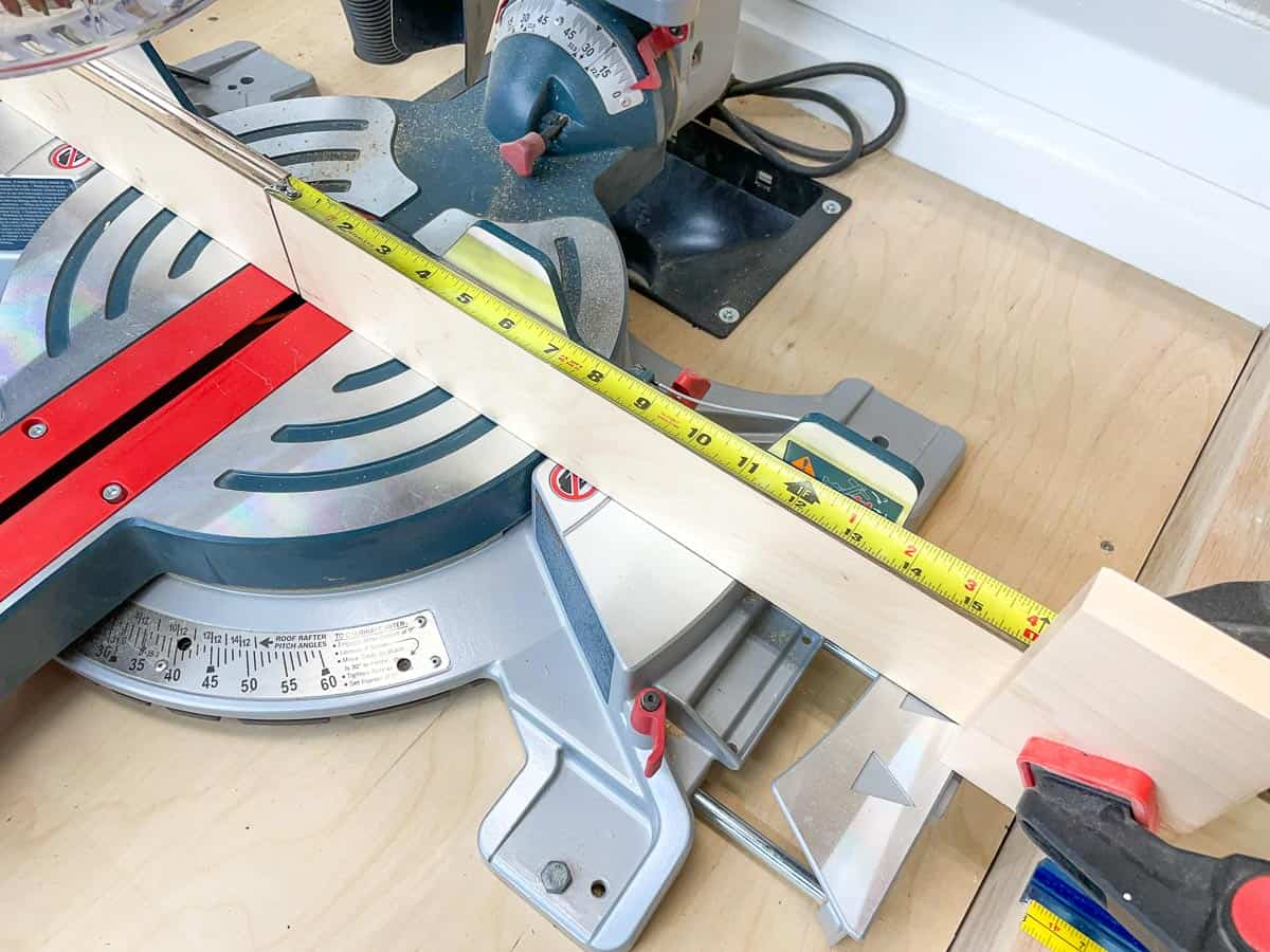 miter saw stop block on extension fence with tape measure to check position