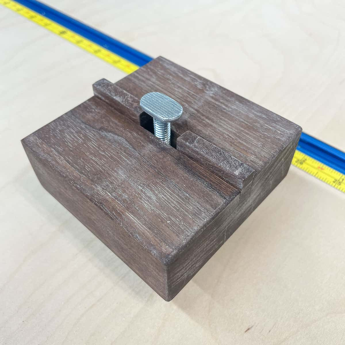 bottom of t track stop block with bolt between two wooden runners
