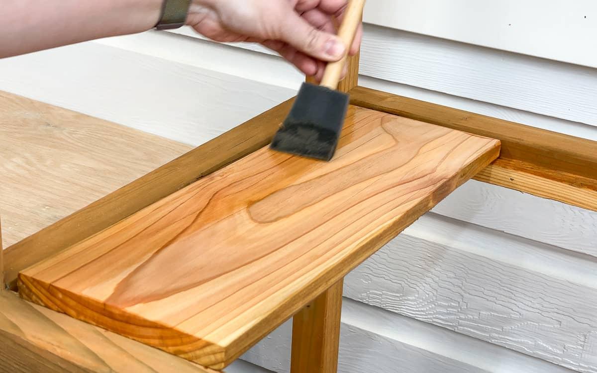 applying spar urethane to the DIY greenhouse shelf slats
