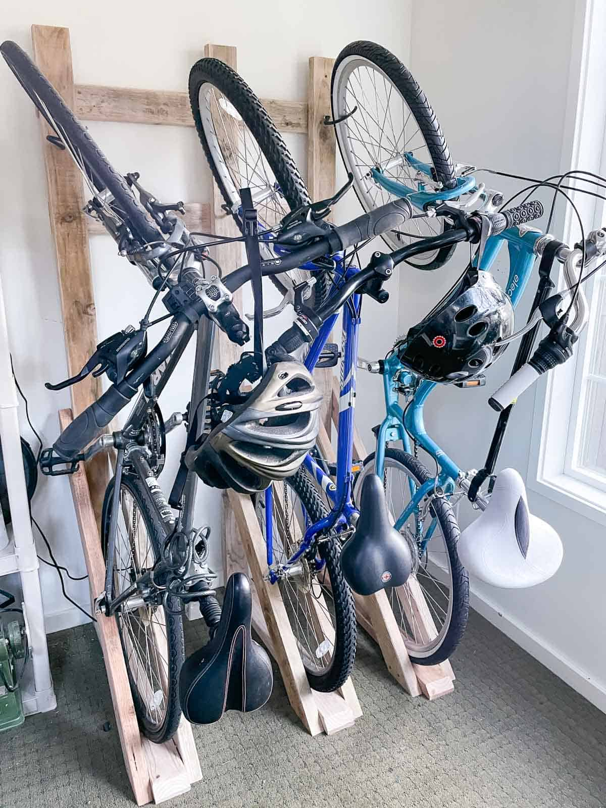 DIY vertical bike rack with three bicycles on wall