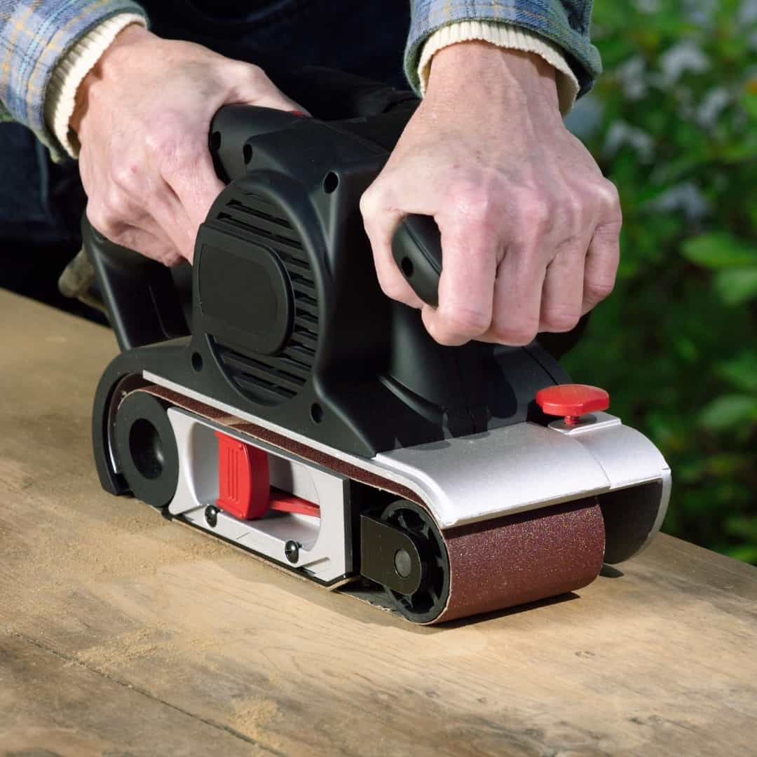 handheld belt sander on rough wood surface