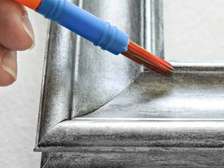 painting a picture frame with a brush