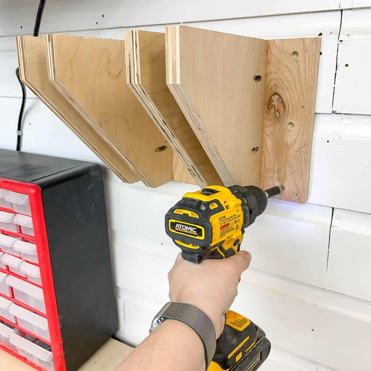 screwing DIY clamp rack to the wall with a cordless drill