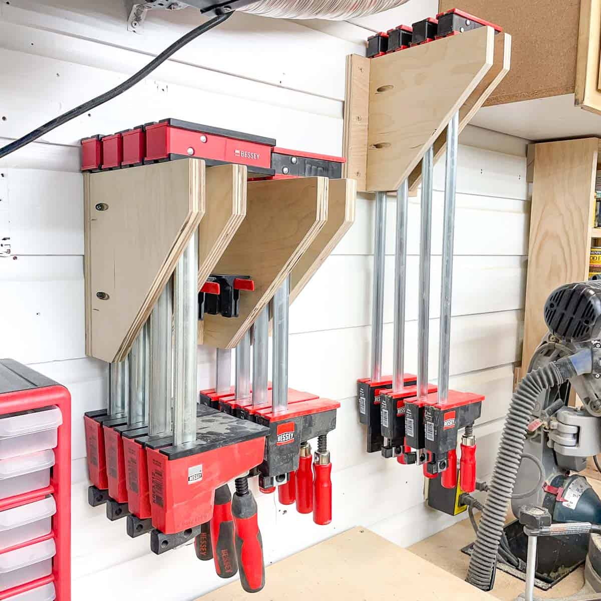 parallel clamp racks on wall behind miter saw station