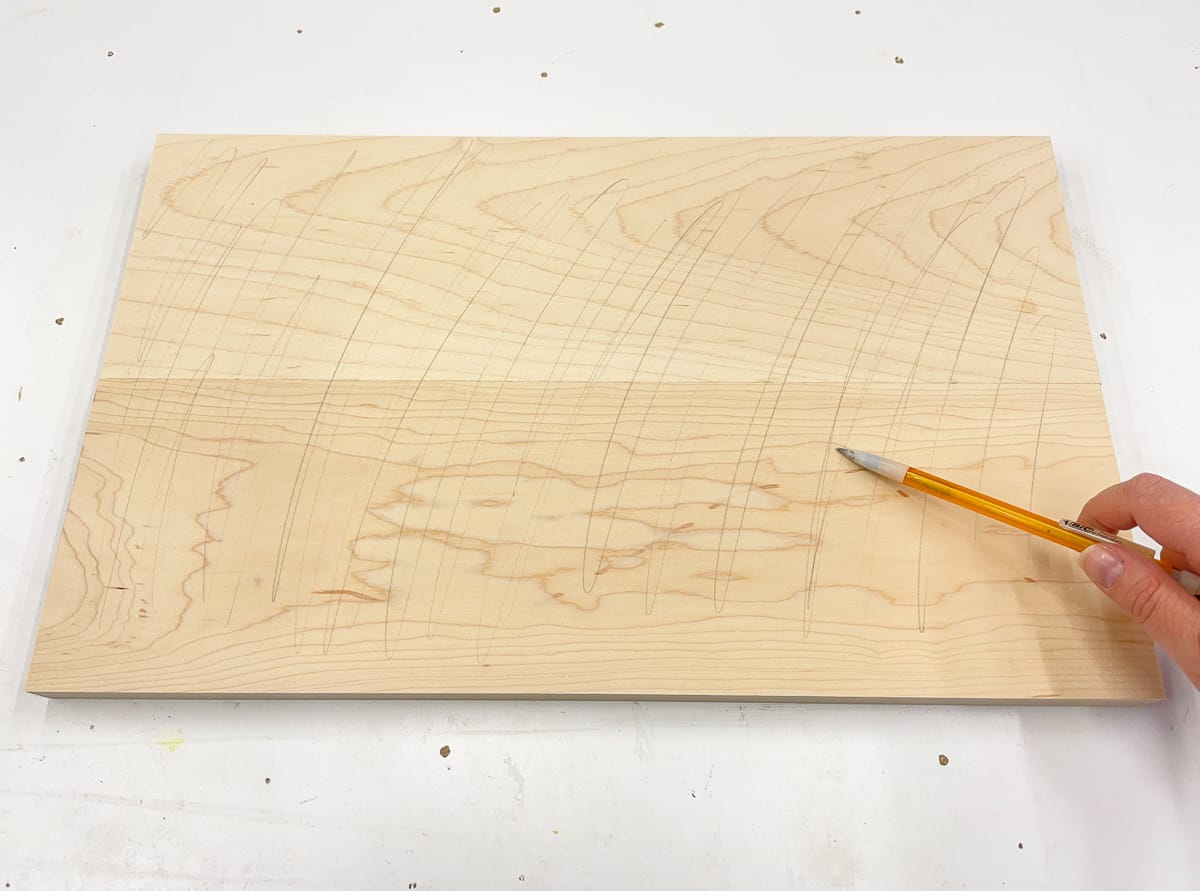 lightly drawing lines with a pencil over surface of the wood before sanding
