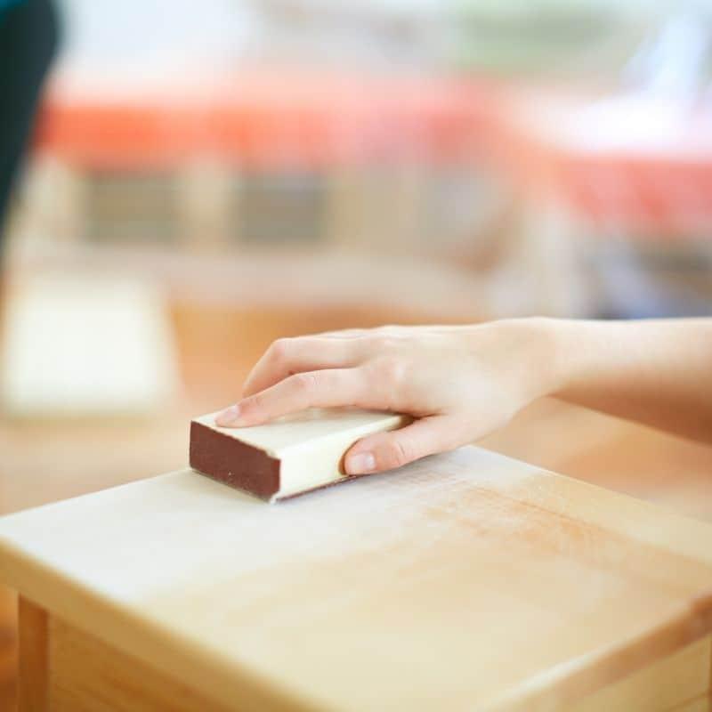 woman's hand sanding wood table top with sanding block