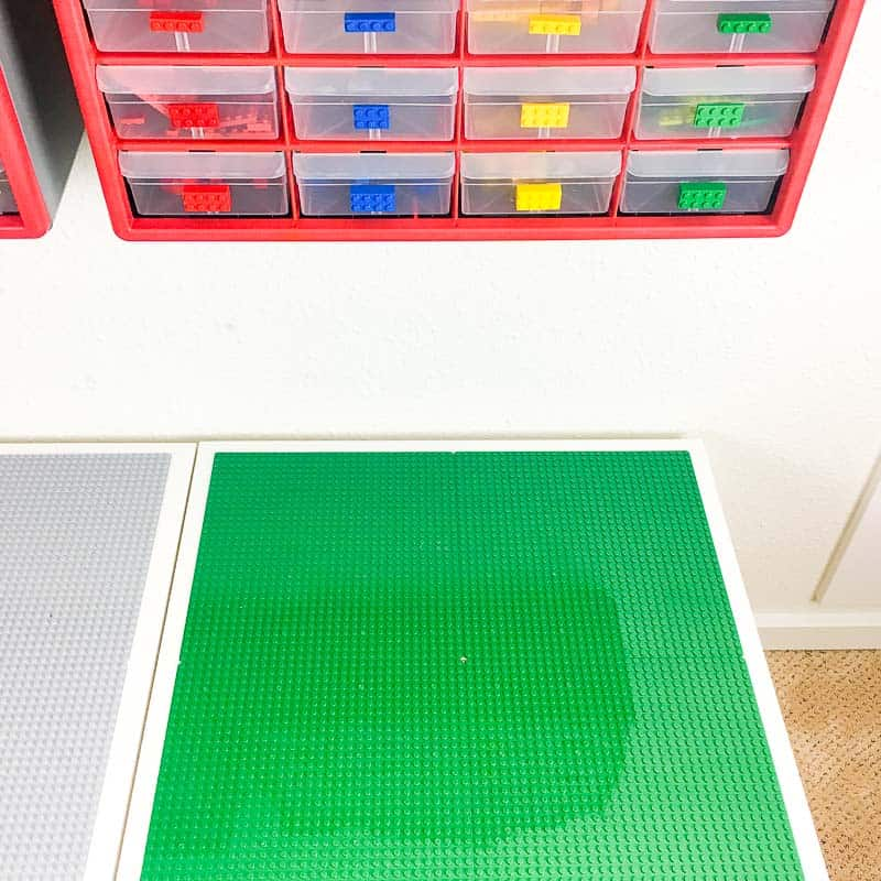 Lego table with small parts bins attached to the wall above