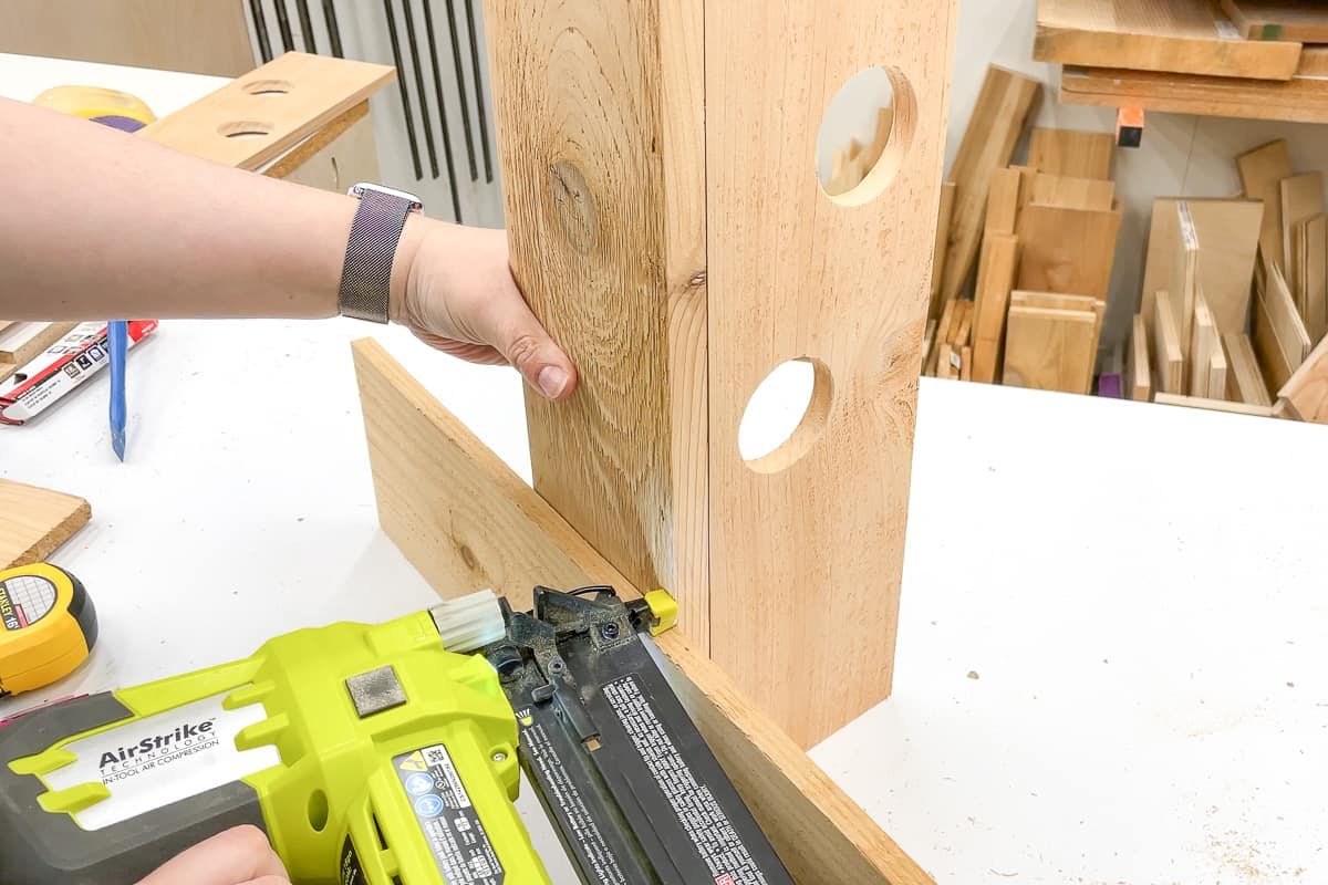 attaching sides of strawberry tower with a brad nailer