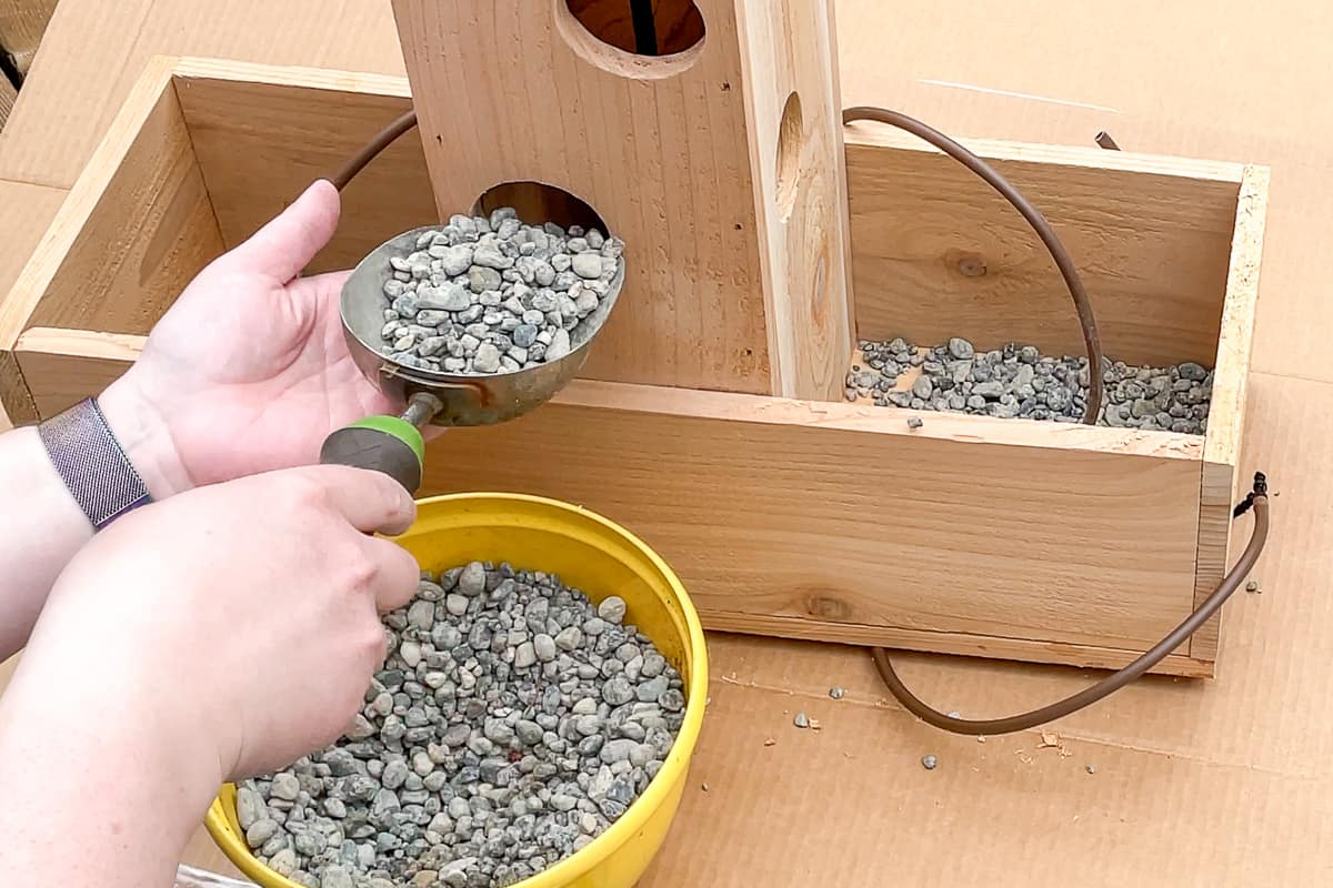 adding pea gravel to the bottom of a strawberry planter for drainage