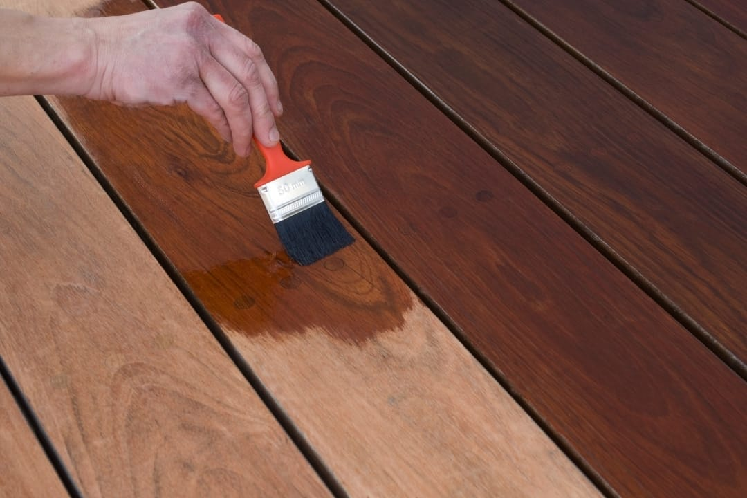 applying new deck stain over old stain