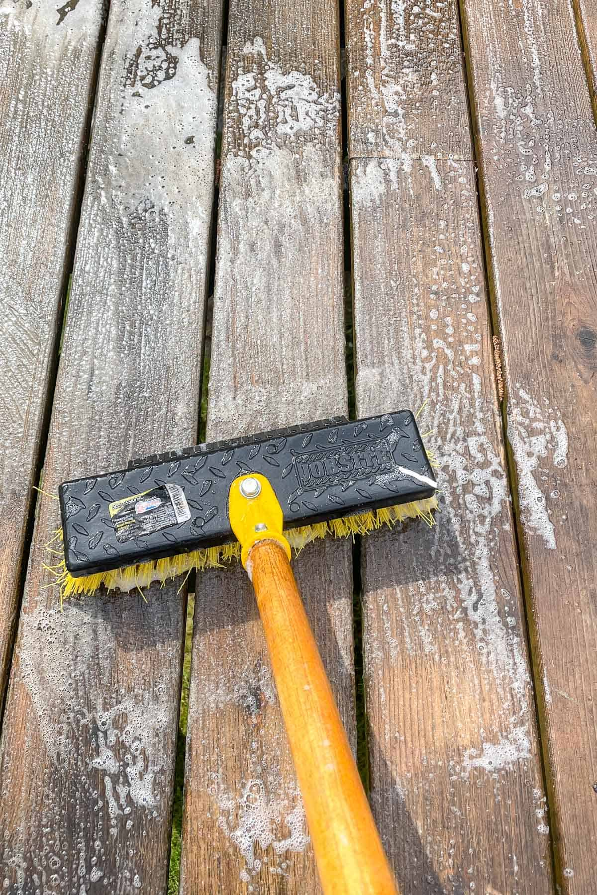 applying deck cleaner to dirty deck with a scrub brush