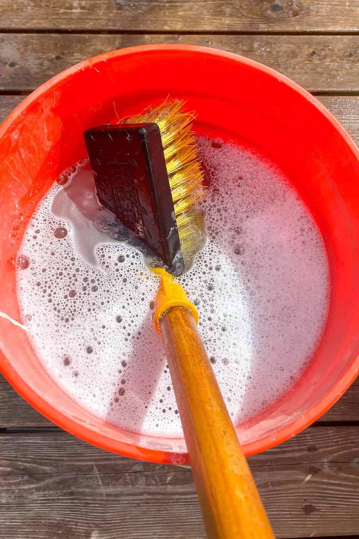 scrub brush in deck cleaner bucket