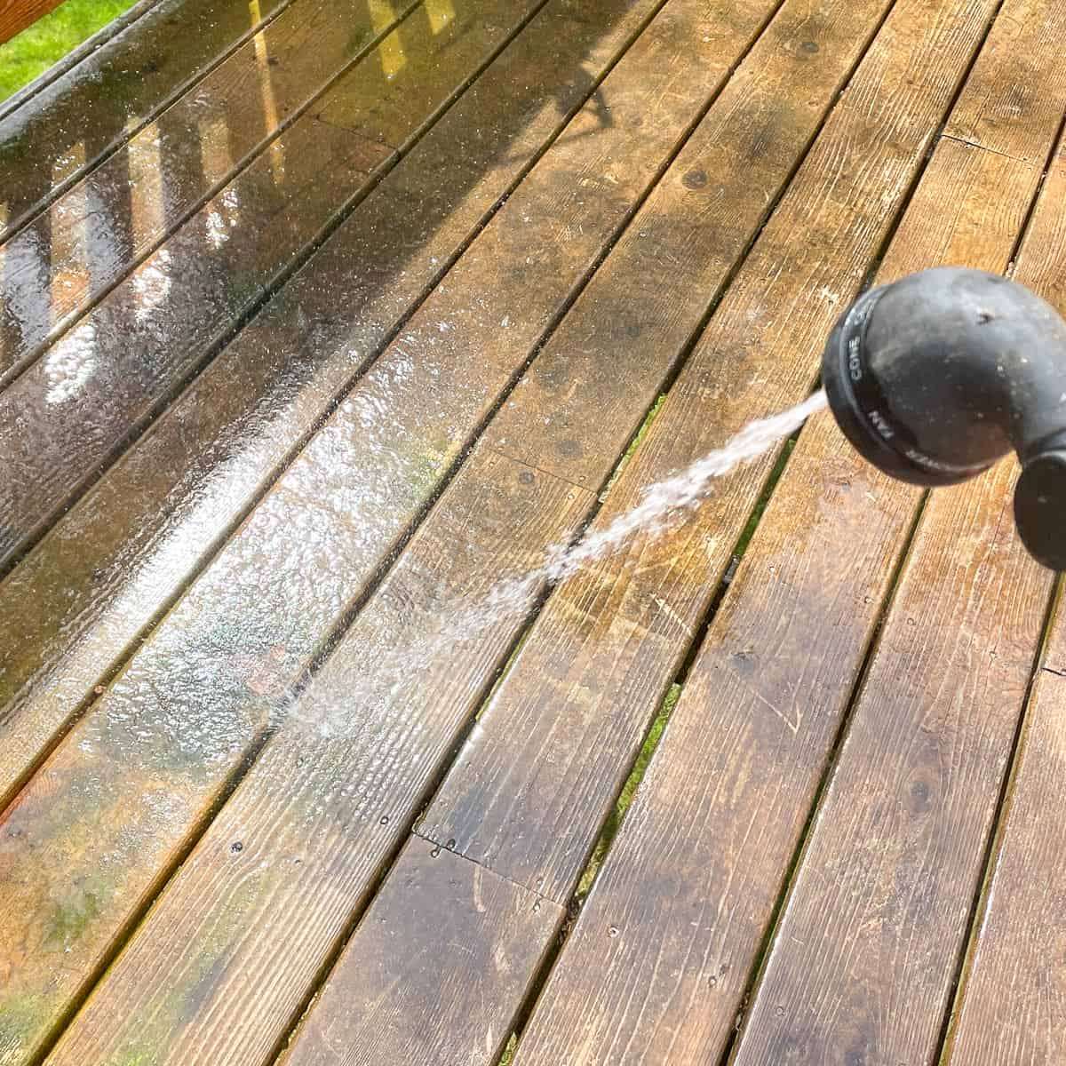 rinsing dirty deck with a hose before cleaning