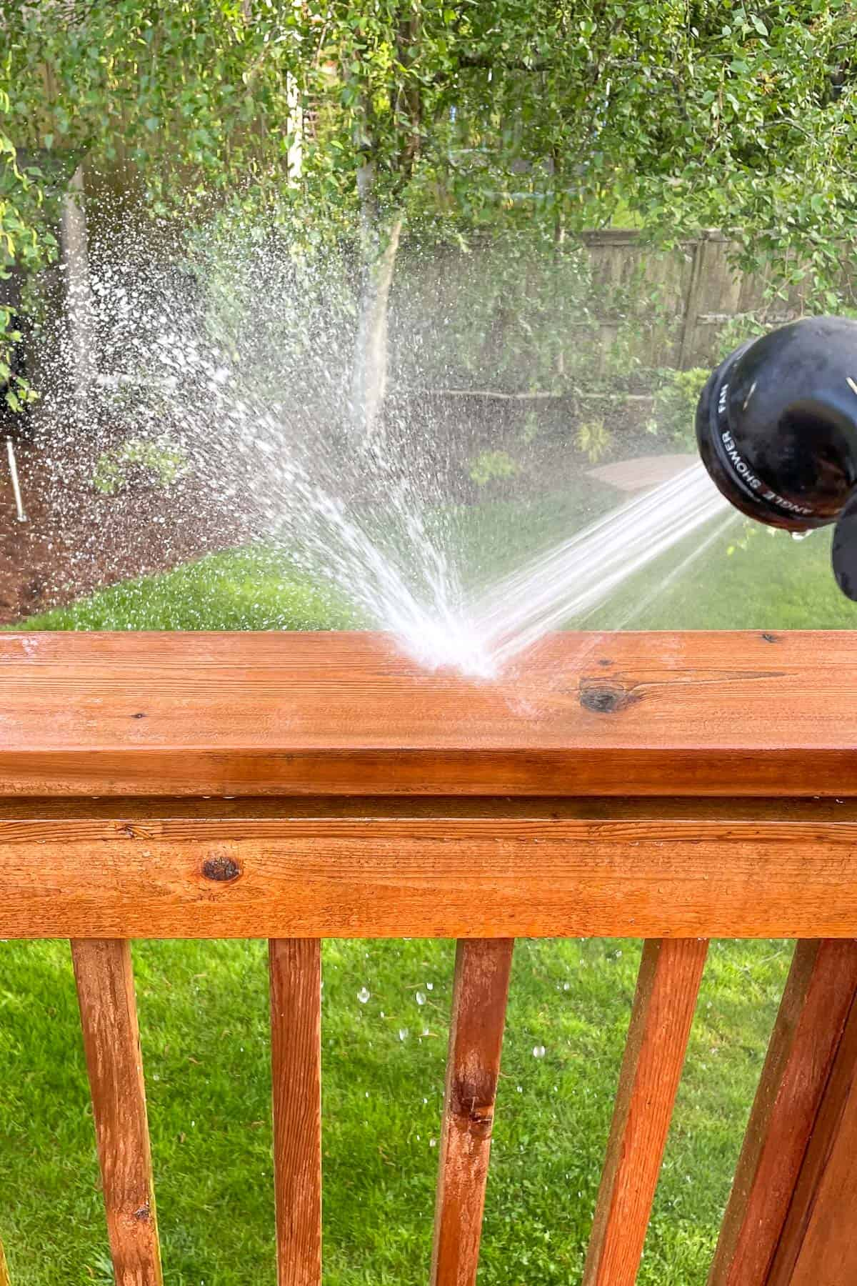rinsing deck railing with a hose after applying cleaner
